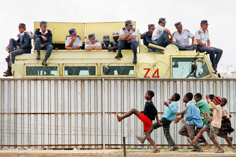 South Africa, Tokoza Township, Johannesburg. 1991. Police watch an ANC rally while children taunt them by toyi-toying on the other side of the fence.