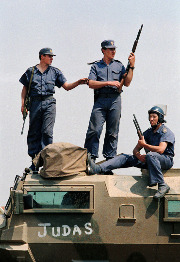 South Africa, East Rand. 1990. Police watch Inkatha Freedom Party members in Tokoza during a period of violence between the ANC the IFP.