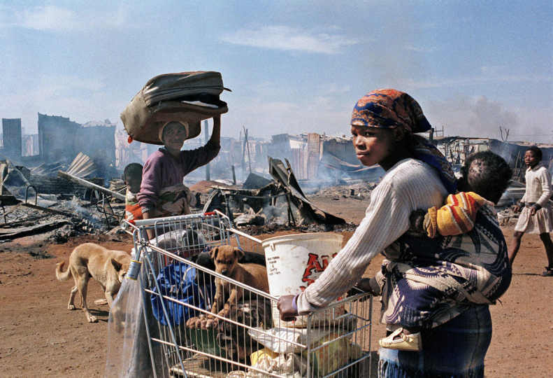 South Africa,  Katlehong Township, Johannesburg. 1990. Women and children gather a few of their belongings after their squatter camp was destroyed during clashes between the ANC and the IFP.