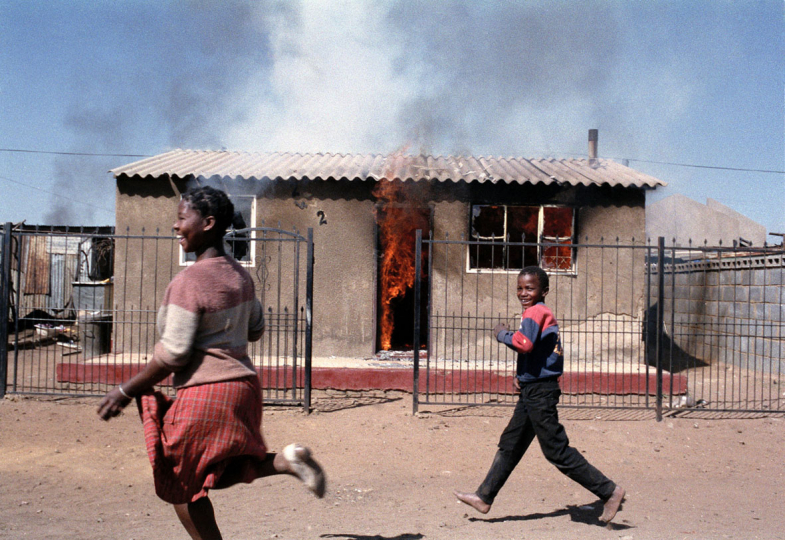 South Africa, Kagiso Township, Johannesburg. 1990. ANC supporters run passed a burning house belonging to an IFP supporter.