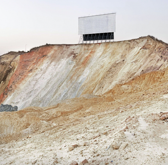 The Top Star Drive-in theatre screen remains standing as the mine dump on which it was build is reworked to extract the remaining gold content. Johannesburg. The drive-in was built in the early 60's and the screen collapsed two days after this image was made. South Africa. 2010.