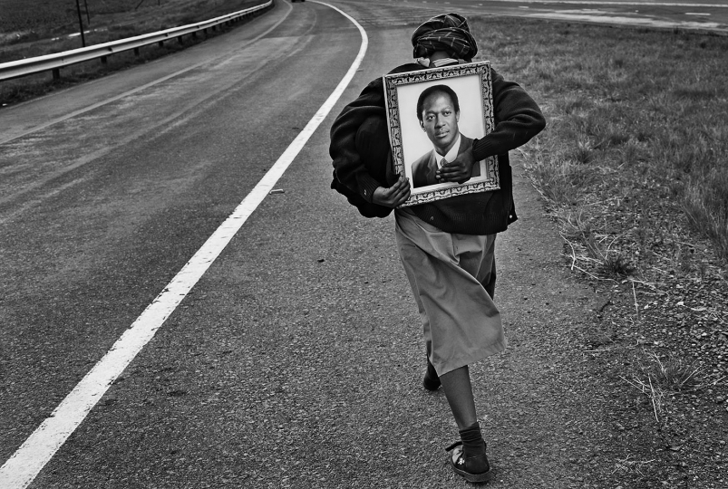 A woman walks towrds a highway hoping to get lift so that she can return home for Christmas. She is carrying a family portrait. Secunda. 2016.