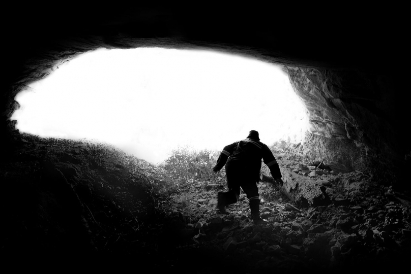 Lovemore Moya (an illegal miner) in an open cave that has been dug by illegal miners in Roodepoort , johannesburg.