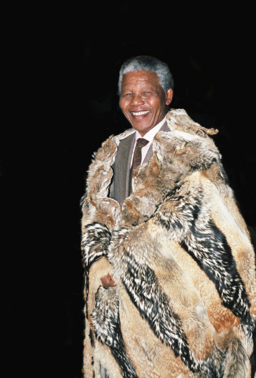 Nelson Mandela is presented with a traditional coat made from furs during a mine workers' conference held in Soweto. South Africa. 1991.
