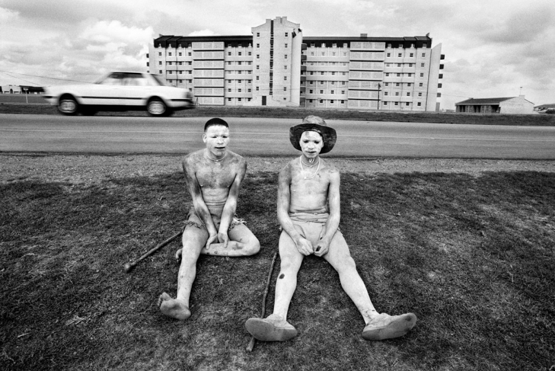 Two Xhosa initiates relax next to the highway. The ritual removal from society and the male circumcision ceremony mark the transition from boyhood to manhood. Port Elizabeth, South Africa. 1994.