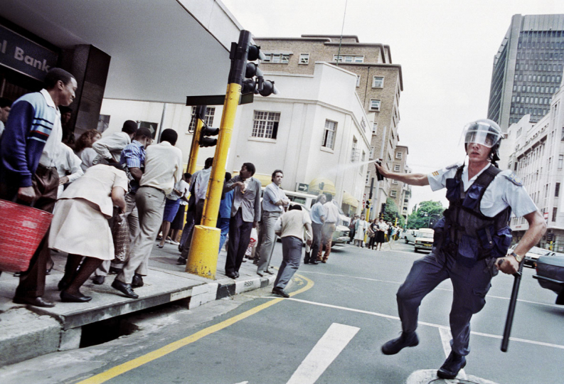 South Africa, Johannesburg, 1990: Policeman teargases a crowd after celebrations in Johannesburg streets following the unbanning of the  African National Congress (ANC).