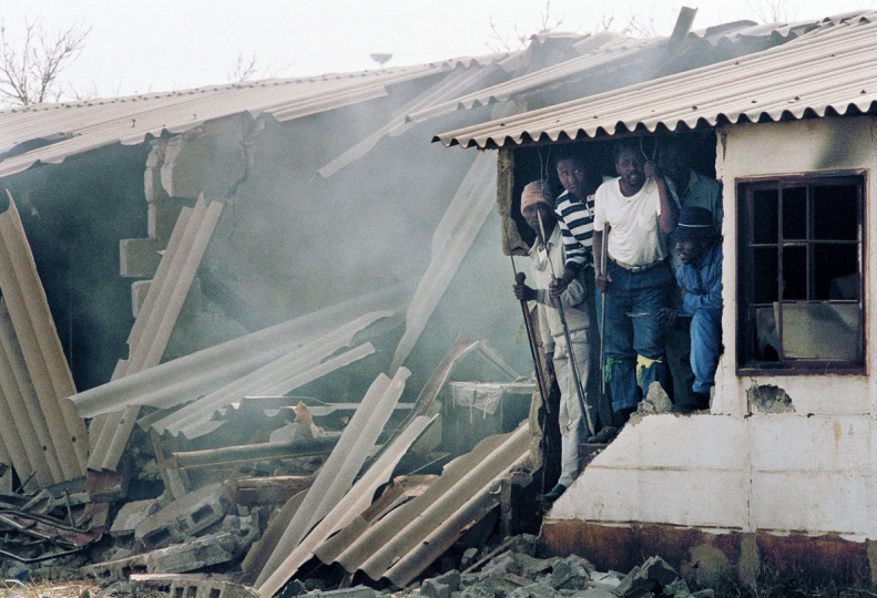 South Africa, Vosloorus Township, Johannesburg. 1990. Inkatha hostel dwellers survey their bombed living quarters.