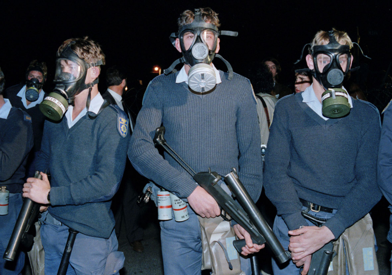 South Africa, Ventersdorp. 1991. Policemen wearing gas masks clash with white right-wing AWB supporters while President F. W. de Klerk speaks to his supporters.