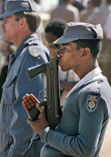 South Africa, Kagiso Township, Johannesburg. 1990 A  policeman waits for orders to shoot during a standoff between ANC supporters and the police.